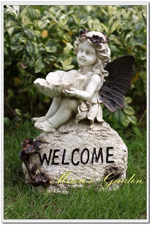 子供天使、ガーデニング雑貨、ガーデニンググッズ、石の上に座って手に大きな花を持った花冠をつけた女の子天使、エンジェルオブジェ、オーナメントフィギア