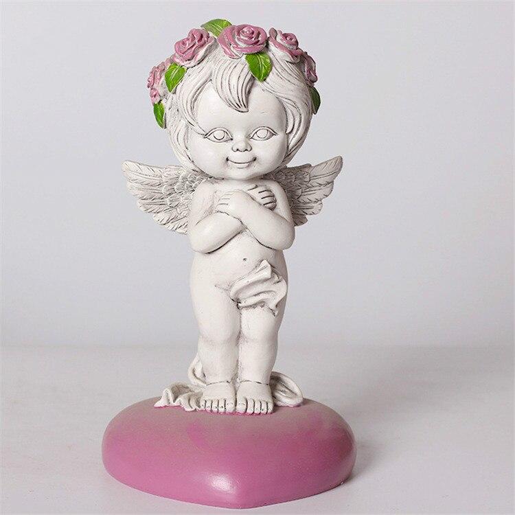 天使置物、エンジェル人形、天使雑貨グッズ、ピンク色のハートの上で頭にピンク薔薇の花冠をつけて心に両手を当て微笑んでいる可愛い天使人形、エンジェルオブジェオーナメントフィギア